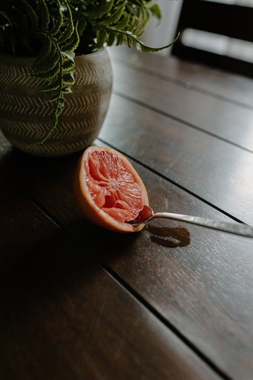 Spoon in fresh grapefruit on wooden table