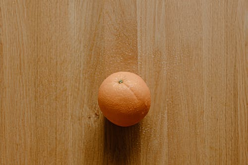 Top view of tasty round orange placed on wooden surface in light room