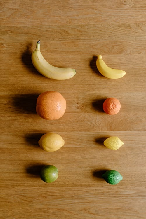Top view of fresh ripe yellow bananas and oranges near lemons and green limes placed on wooden floor in light room