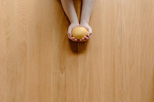 Unrecognizable child demonstrating lemon in hands on wooden surface