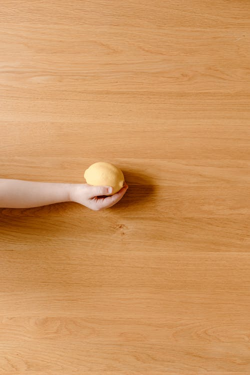 Faceless kid with lemon in hand on wooden floor