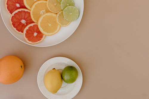 Top view of sliced red grapefruits with oranges near yellow lemons and green limes on plates on beige surface in light place