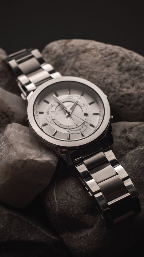 Black and white from above of shiny silver wristwatch with white clock face placed on pile of rough stones