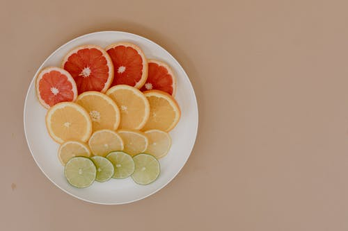 Plate with sliced lemons and oranges with grapefruits and limes