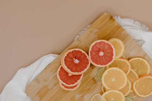 Top view of wooden cutting board with sliced oranges and red grapefruits near green limes and yellow lemons on white textile on beige surface in light studio