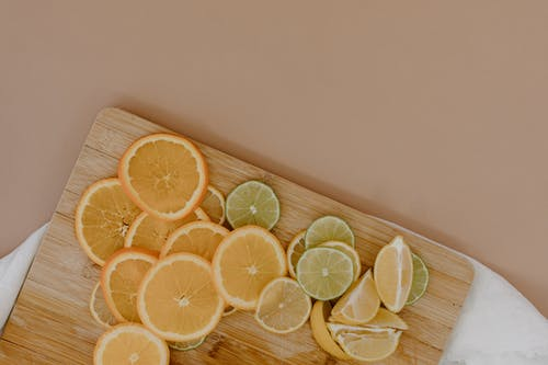 Top view of sliced with yellow lemons near oranges and green limes on wooden cutting board on white napkin on beige surface in light place