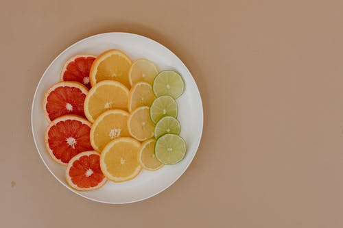 Top view of sliced red grapefruits with yellow lemons near oranges and green limes on plates in light place on beige surface