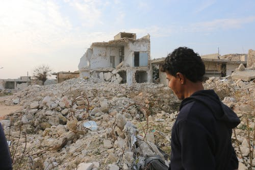 Side view of ethnic male walking on street near pile of stone and remains of damaged houses against demolished building