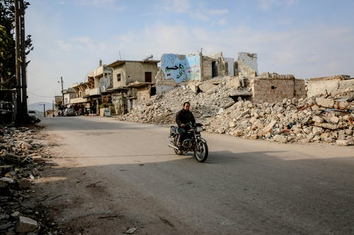 Active man riding motorcycle on empty straight roadway along destroyed buildings and piles of ruined houses in district of town