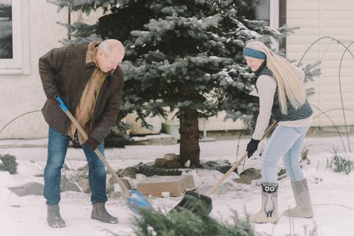 Man and Woman Holding Shovels