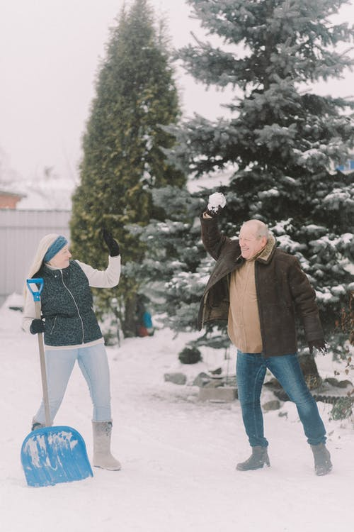 Man and Woman Standing on a Snow Covered Ground