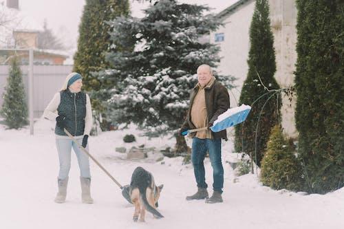 Couple Shoveling Snow with Dog