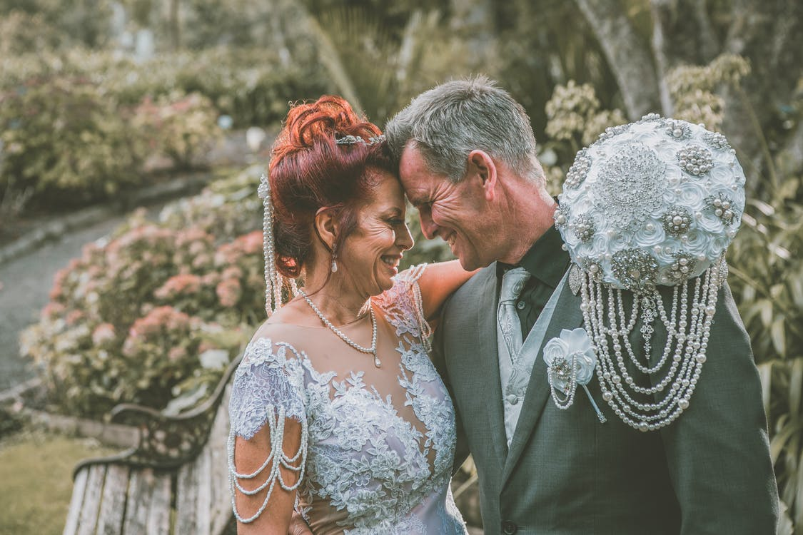 Side view of happy middle aged bride and groom in elegant outfits smiling and looking at each other while touching foreheads in green park on wedding day