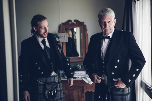 Focused young and senior Scottish men wearing Highland traditional dress with kilt jacket and sporran while standing together in classic styled room