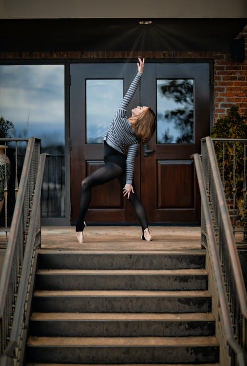 Full body gorgeous fit female dancer in leggings standing gracefully with arms raised on doorsteps