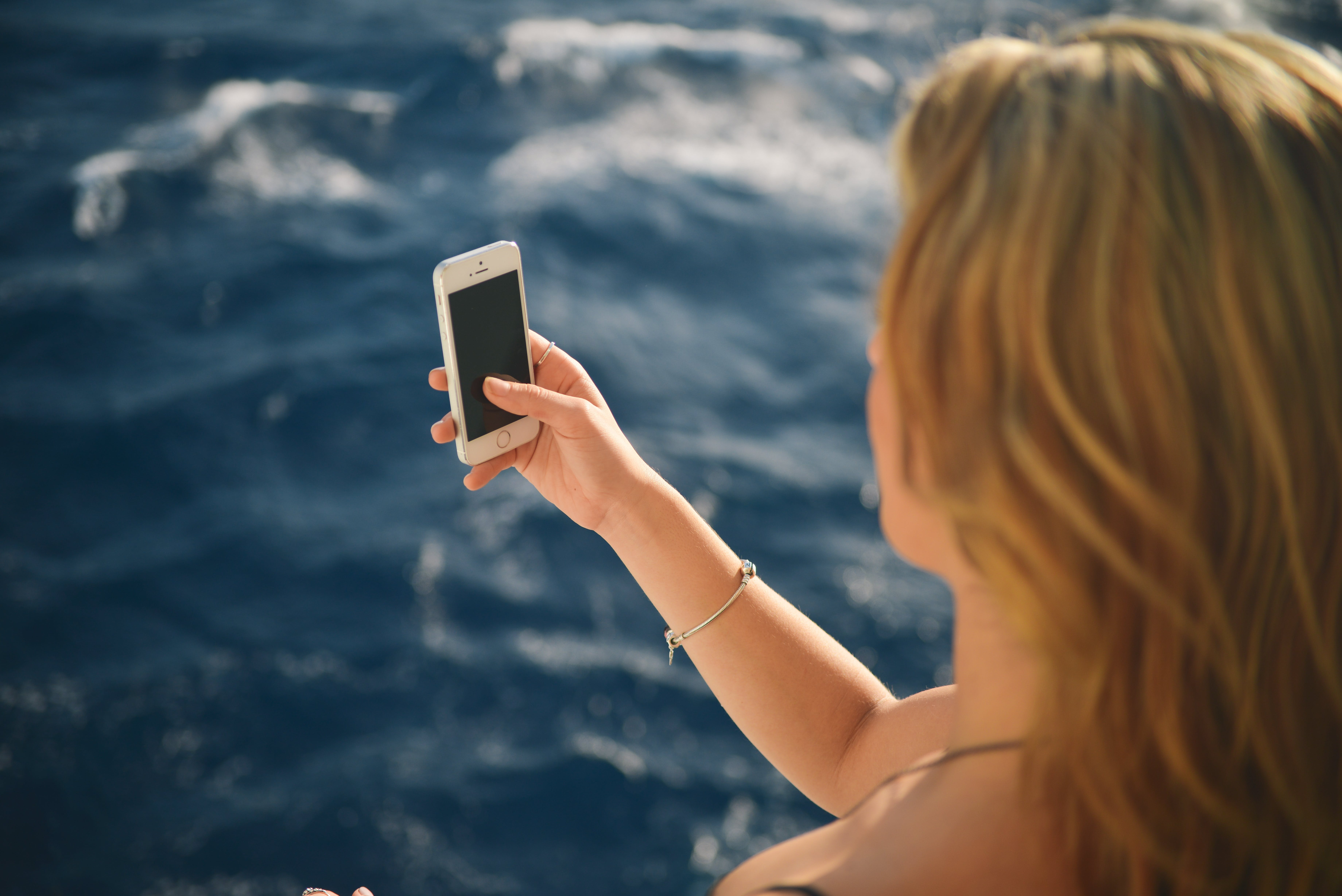 Woman Holding Silver Iphone 5s in Black Screen Near Body of Water