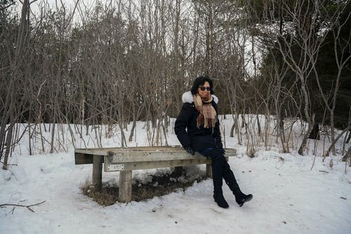 Woman Sitting on a Wooden Bench