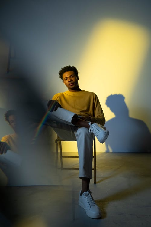 Man in Yellow Sweatshirt and White Pants Sitting on Chair