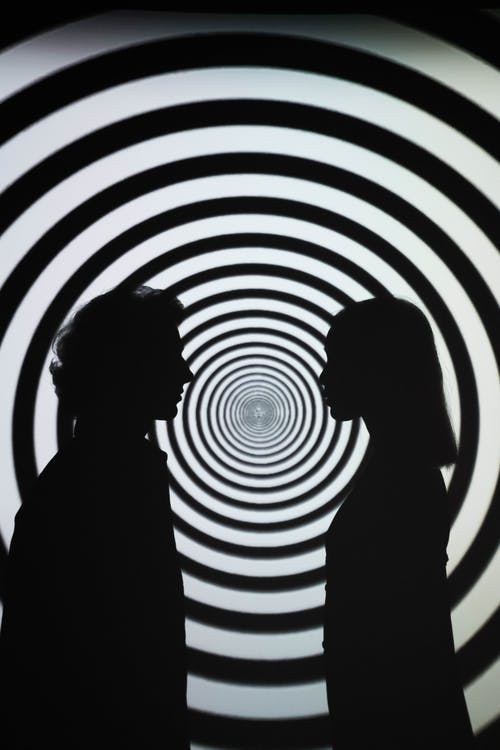 Silhouette of 2 People Standing in Front of Round White and Black Stripe Wall