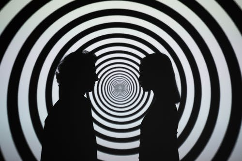 Silhouette of 2 Person Standing in Front of White and Black Stripe Wall