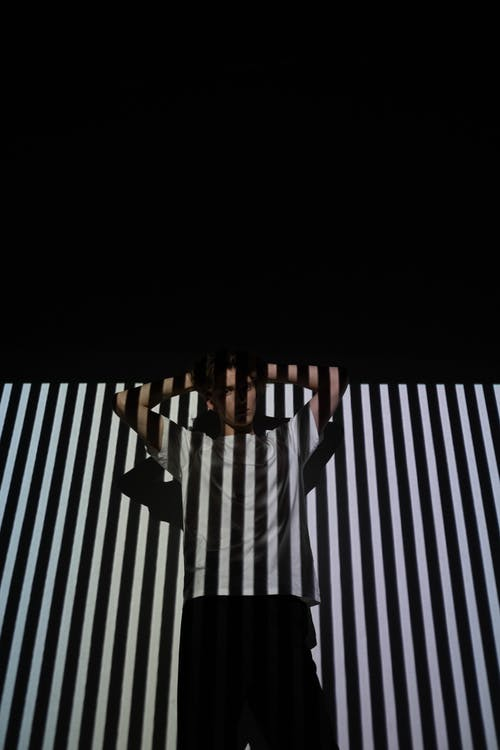 Person in Black and White Striped Wall