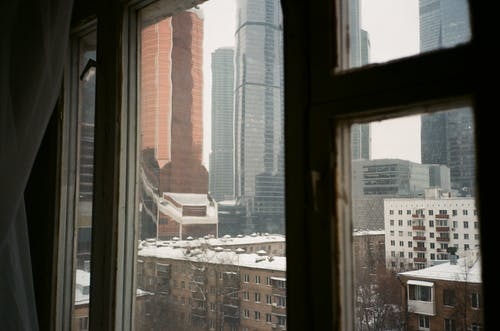 Through apartment window view of modern urban city architecture with snowy residential buildings and skyscrapers on overcast winter day