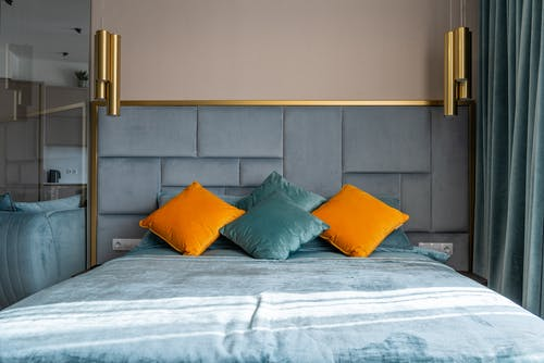 Soft bed with turquoise blanket and multicolored pillows placed in modern bedroom with curtains and hanging decorative lamps at home