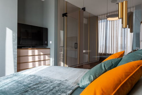 Interior of modern bedroom with colorful pillows on bed placed against TV with drawer near glass door in contemporary apartment