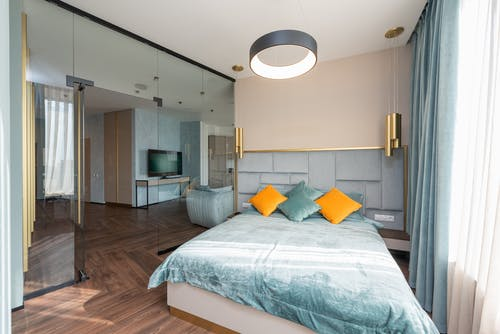 Soft comfortable bed with cushions in modern spacious bedroom with parquet floor and glass wall