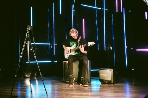 Full body focused young professional male musician playing bass guitar while sitting on floor speaker on stage during rehearsal