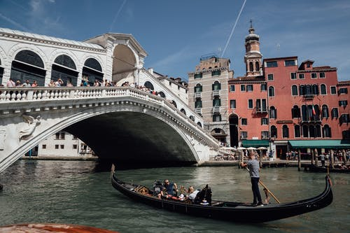 Travelers floating on gondola on Grand canal near famous bridge among aged residential buildings in Venice during vacations in Italy