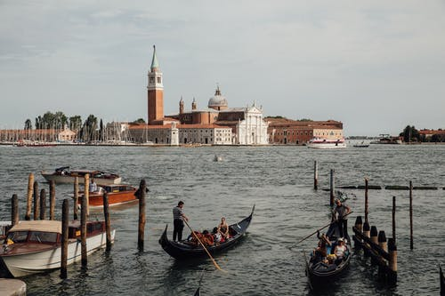 People floating on boats on rippling water against aged buildings with tower and dome in Venice during trip to Italy