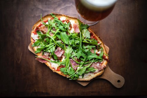 From above of tasty toast with cured meat slices and melted cheese with fresh herb leaves on brown background