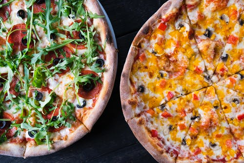 Delicious pizzas with vegetable slices and arugula leaves