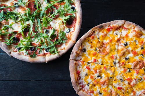 Overhead view of delicious pizzas with mushroom and pepperoni pieces under fresh herb leaves on dark background