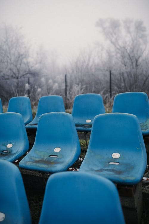 Blue Plastic Chairs on Snow Covered Ground