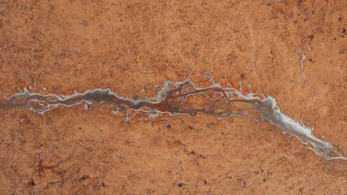 Top view of textured background representing icy creek with drops on barren terrain in daylight