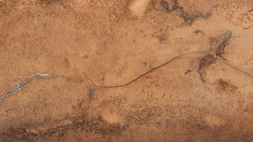 Drone view of textured background representing frozen creek on rough brown land with spots in daytime