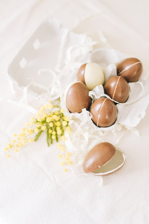 Brown Eggs In A White Carton Beside Yellow Flowers