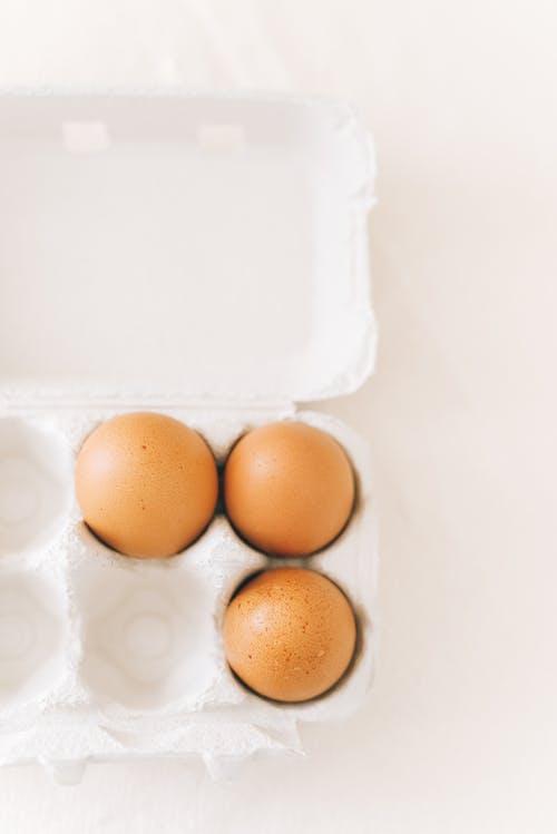 Three Brown Eggs In A Carton