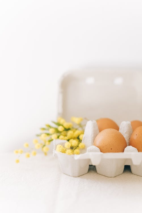 Crop Tray Of Brown Eggs With Flowers