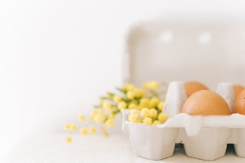 Brown Eggs And Yellow Flowers On A Carton