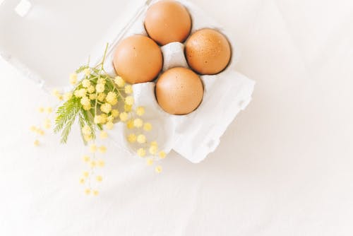 Brown Eggs And Yellow Flowers On White Surface