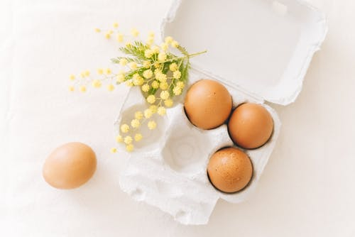 Yellow Flowers And A Carton Of Brown Eggs