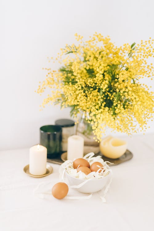Yellow Flowers And Lighted Candles Beside A Bowl Of Brown Eggs On Table