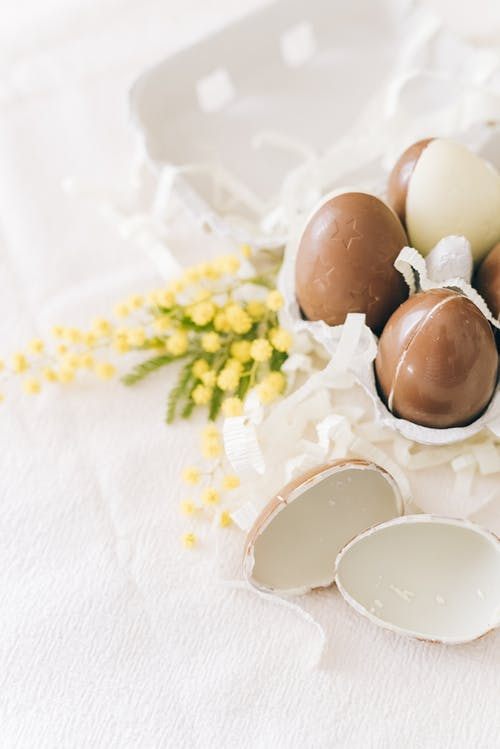 Brown Eggs And Yellow Flowers On Table