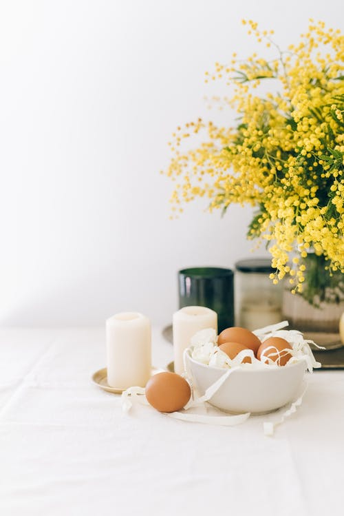 White Candles  And Brown Eggs In A Bowl On Table