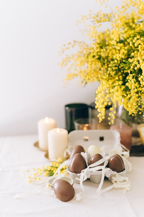 White Candles And Brown Eggs on White Table
