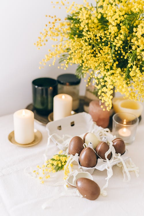 Yellow Flowers And Brown Eggs on White Table