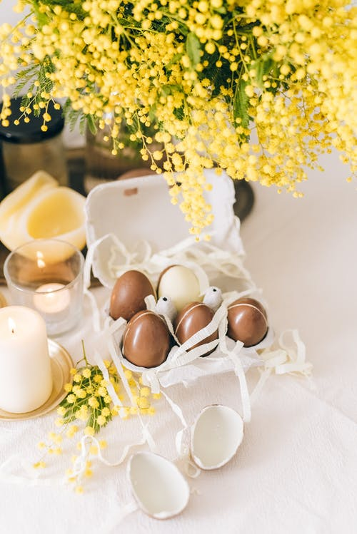 Brown Eggs On A Carton With Flowers On Table